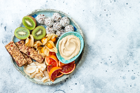 Healthy vegan dessert snacks - protein granola bars, homemade raw energy balls, cashew butter, toasted coconut chips, cape gooseberry, kiwi, blood orange. Concept of healthy sweets for children. Reklamní fotografie