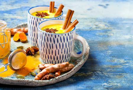 Kurkuma gouden melk latte met kaneelstokjes en honing. Detox, immuunversterkend, ontstekingsremmend gezond gezellig drankje