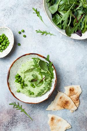 Hummus di piselli da spalmare o inzuppare con foglie di insalata mista. Antipasto estivo crudo sano, spuntino vegano e vegetariano.