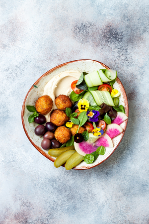 Middle eastern lunch Buddha bowl with hummus, falafel, tomato and greens salad, olives, pickles and edible flowers