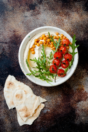 Homemade hummus with roasted cherry tomatoes and pita bread. Middle Eastern traditional and authentic arab cuisine. Top view, flat lay, overhead