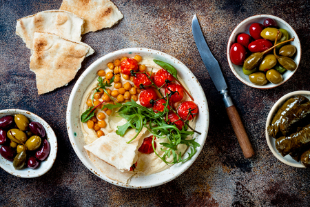 Homemade hummus with roasted cherry tomatoes, olives, dolma and pita bread. Middle Eastern traditional and authentic arab cuisine. Stock Photo