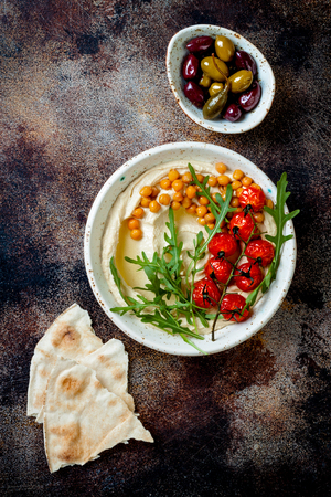 Homemade hummus with roasted cherry tomatoes and olives. Middle Eastern traditional and authentic arab cuisine. Top view