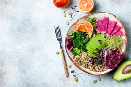 Vegan, detox Buddha bowl with quinoa, micro greens, avocado, blood orange, broccoli, watermelon radish, alfalfa seed sprouts. Top view, flat lay, copy space