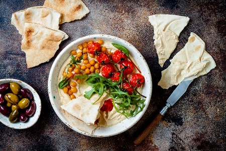 Homemade hummus with roasted cherry tomatoes, olives and pita bread. Middle Eastern traditional and authentic arab cuisine. Top view, flat lay, overhead Stock Photo
