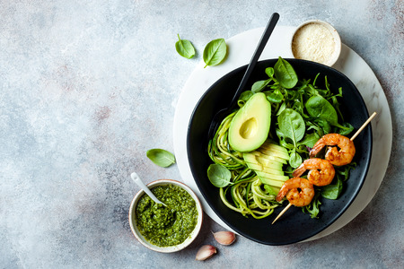 Detox Buddha bowl with avocado, spinach, greens, zucchini noodles, grilled shrimps and pesto sauce. Vegetarian vegetable low carb lunch bowl. Banque d'images