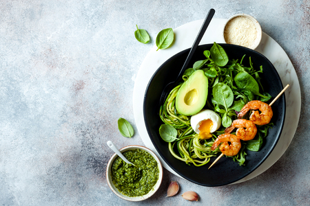 Buddha bowl with soft boiled egg, avocado, greens, zucchini noodles, grilled shrimps and pesto sauce. Vegetarian vegetable low carb lunch bowl.