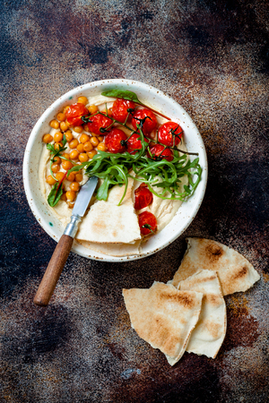 Homemade hummus with roasted cherry tomatoes and pita bread. Middle Eastern traditional and authentic arab cuisine. Stock Photo