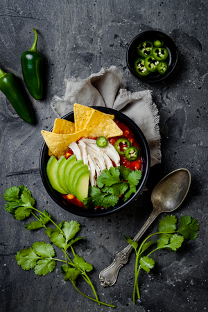 Chicken tortilla chili soup with nachos, avocado, lime, jalapeno. Mexican traditional dish