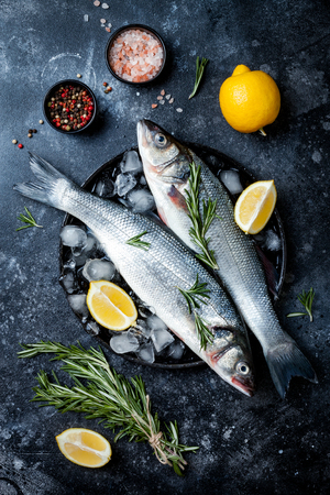 Fresh raw seabass fish on black stone background with spices, herbs, lemon and salt. Culinary seafood background with ingredients for cooking. Top view Reklamní fotografie