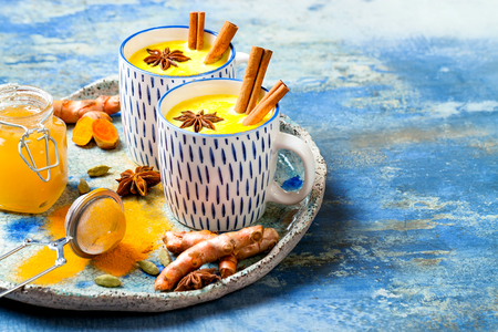 Turmeric golden milk latte with cinnamon sticks and honey. Detox, immune boosting, anti inflammatory healthy cozy drink