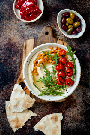Homemade hummus with roasted cherry tomatoes, pickles and olives. Middle Eastern traditional and authentic arab cuisine. Top view Stock Photo