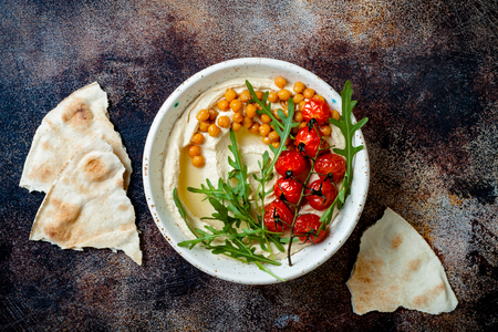 Homemade hummus with roasted cherry tomatoes. Middle Eastern traditional and authentic arab cuisine. Top view, overhead