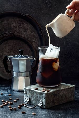 Cold refreshing iced coffee in a tall glass and coffee beans on dark background. Pouring cream into glass with iced coffee Foto de archivo - 127869003