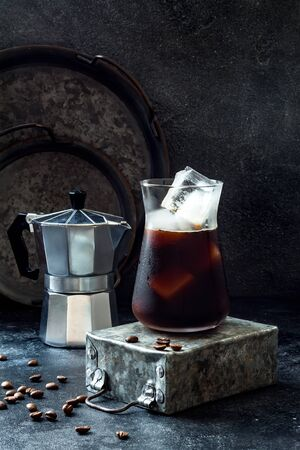 Cold refreshing iced coffee in a tall glass and coffee beans on dark background.