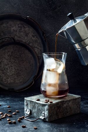 Cold refreshing iced coffee in a tall glass and coffee beans on dark background. Pouring coffee from moka pot into glass with ice cubes Foto de archivo - 127869023