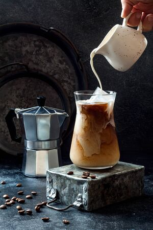 Cold refreshing iced coffee in a tall glass and coffee beans on dark background. Pouring cream into glass with iced coffee