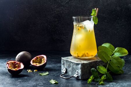 Passionfruit iced green tea or lemonade with lime and mint. Tropical refreshing cold drink for summer