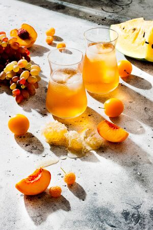 Refreshing peach ice tea or lemonade in glasses. Summer yellow fruit cocktail.