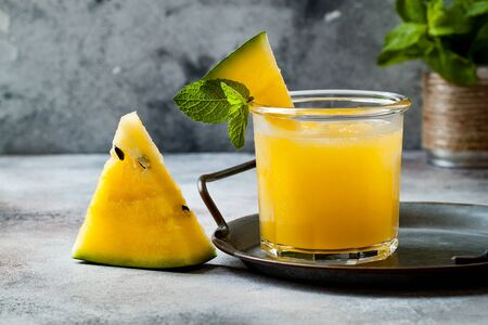 Glass of fresh golden watermelon juice or smoothie with slices of watermelon.