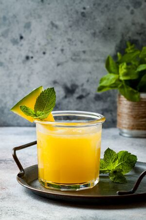 Glass of fresh golden watermelon juice or smoothie with slices of watermelon. Refreshing cold summer fruit drink