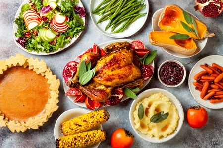 Thanksgiving dinner table with roasted whole chicken or turkey, green beans, mashed potatoes, cranberry sauce and grilled autumn vegetables. Top view, overhead.  Stok Fotoğraf