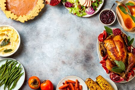 Thanksgiving dinner table with roasted whole chicken or turkey, green beans, mashed potatoes, cranberry sauce and grilled autumn vegetables. Top view, frame.  Stock Photo