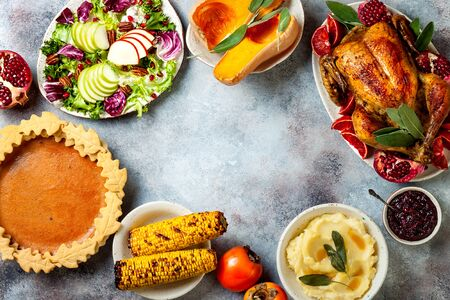 Thanksgiving dinner table with roasted whole chicken or turkey, green beans, mashed potatoes, cranberry sauce and grilled autumn vegetables. Top view, frame. Stok Fotoğraf
