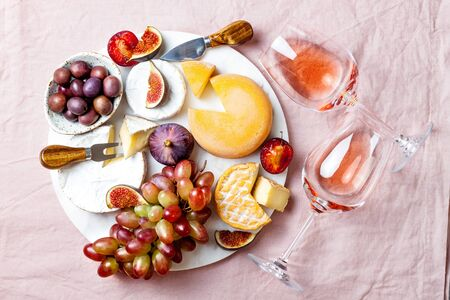 Appetizers, antipasti snacks and rose wine in glasses. Cheese and fruit platter on marble board over pink linen tablecloth background. Top view