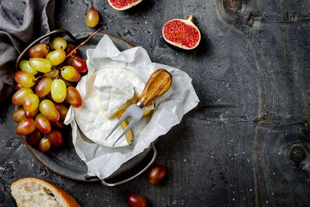 Brie cheese, figs, green grapes. Wine appetizers, antipasti snacks. Cheese and fruit platter on grey rustic background. Top view Stock fotó