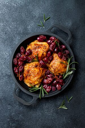 Gebratene Hähnchenschenkel mit roten Trauben auf Pfanne über schwarzem Schieferstein Standard-Bild