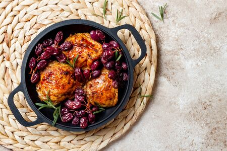 Roasted chicken legs with red grapes on pan over light beige Stock Photo