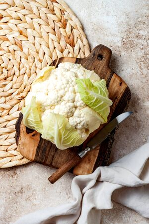 Fresh raw cauliflower on wooden cooking board. Top view, copy space
