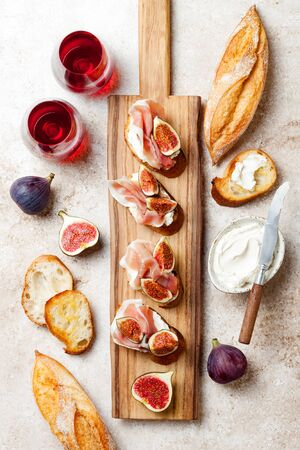 Crostini with prosciutto, cream cheese and figs on wooden board.