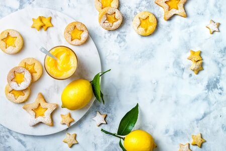 Linzer Christmas cookies filled with lemon curd and dusted with sugar on white marble board Reklamní fotografie