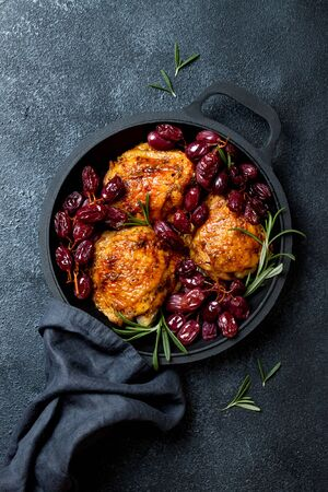 Roasted chicken legs with red grapes on pan over black slate stone Stock fotó