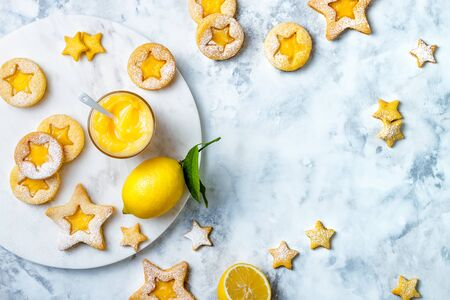 Linzer Christmas cookies filled with lemon curd and dusted with sugar on white marble board Stock fotó - 132541446