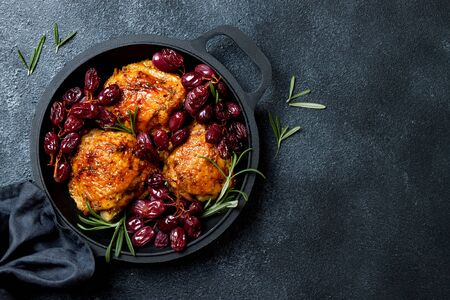 Roasted chicken legs with red grapes on pan over black slate stone background