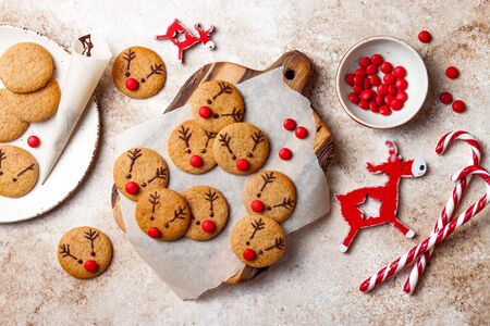 Cooking Christmas gingerbread. Decorating red nosed reindeer cookies with chocolate buttons and melted chocolate. Festive homemade decorated sweets 스톡 콘텐츠