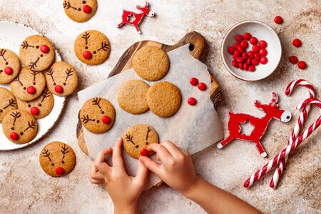 Cooking Christmas gingerbread.  Childs hand decorating red nosed reindeer cookies with chocolate buttons and melted chocolate. Festive homemade decorated sweets Stock fotó