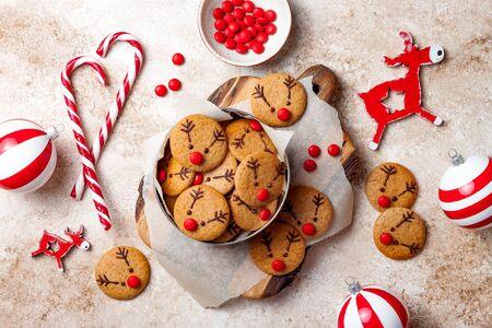 Weihnachtslebkuchen kochen. Verzierte rotnasige Rentierkekse mit Schokoladenknöpfen und geschmolzener Schokolade. Festliche hausgemachte dekorierte Süßigkeiten