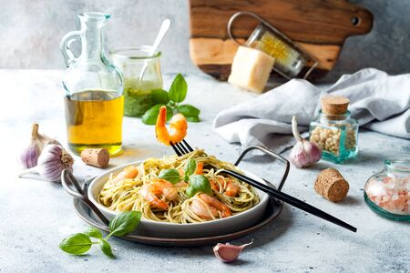 Italian pasta spaghetti with grilled shrimps, pesto sauce and fresh basil leaves