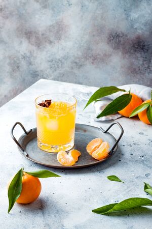 Spicy winter yellow orange cocktail or mocktail with fresh tangerines and anise on grey background. Christmas and New Year holiday welcome drink, copy space