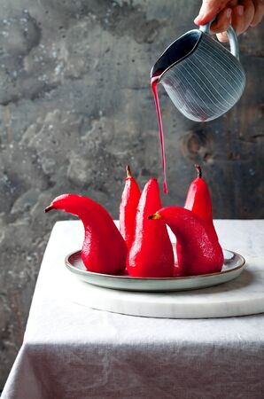 Spiced hibiscus or red wine poached pears. Delicious winter french dessert Stock fotó