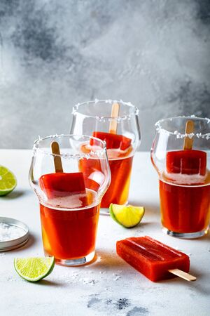 Latin american beer drink Michelada with salt rim and spicy tomato juice . Summer alcohol cocktail michelada or Mexican bloody beer.