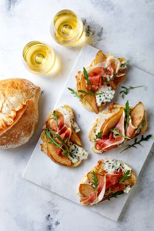 Appetizer crostini, tapas, open faced sandwiches with pear, prosciutto, arugula and blue cheese on white marble board. Delicious snack, appetizers