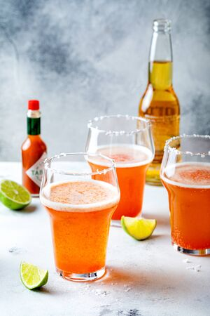 Latin american beer drink Michelada with salt rim and spicy tomato juice. Summer alcohol cocktail michelada or Mexican bloody beer.