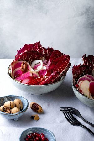 Colorful pink salad with apple, radicchio, pecan nuts, watermelon radish, fennel and pomegranate. Healthy vegetarian meal.