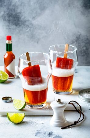 Latin american beer drink Michelada with salt rim and spicy tomato juice  . Summer alcohol cocktail michelada or Mexican bloody beer. 版權商用圖片 - 148223421