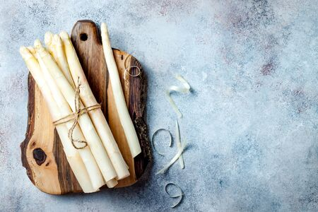 Bunch of raw white asparagus served on wooden board. Top view, copy space 版權商用圖片